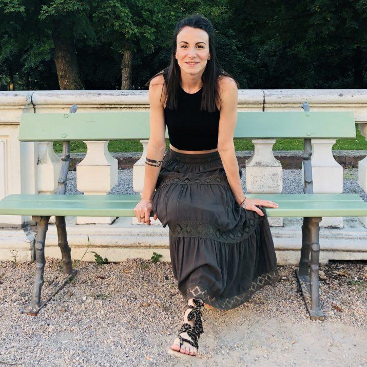 Junge Frau auf einer Parkbank in einem sommerlichem Outfit mit dunklem Oberteil, olivefarbenem Rock und Sandalen.
